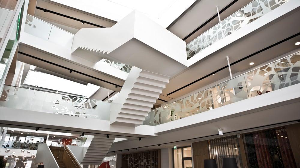 Interiør i næringsbygg med en ekstrem trappeløsning for å illustrere at byggets egenskaper påvirker valg av adgangskontroll - trådløs eller kablet.