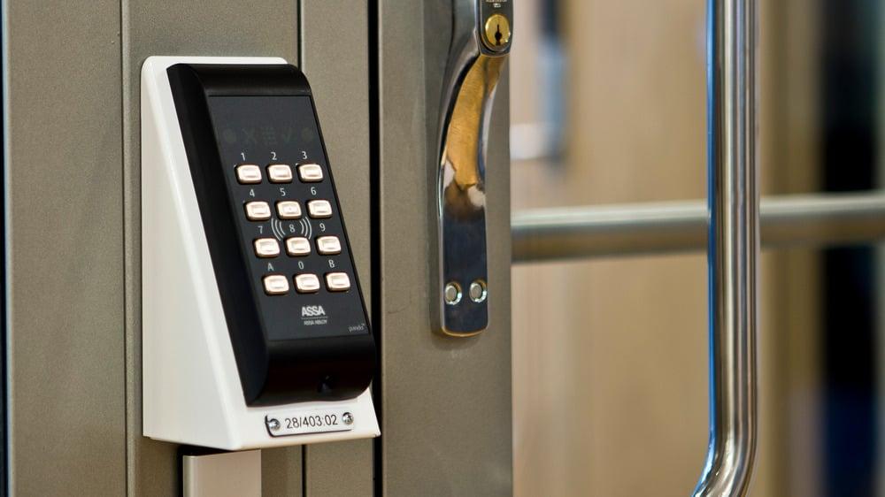 Kortleser og kodepanel for ARX adgangskontrollsystem på siden av dør i glass og stål.