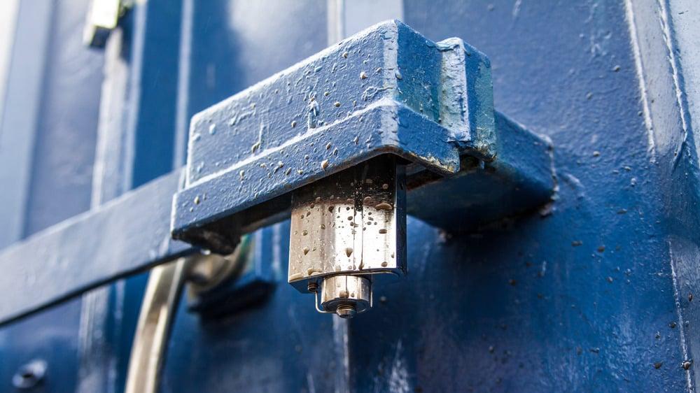 Elektromekanisk hengelås av typen Cliq på en blå container.
