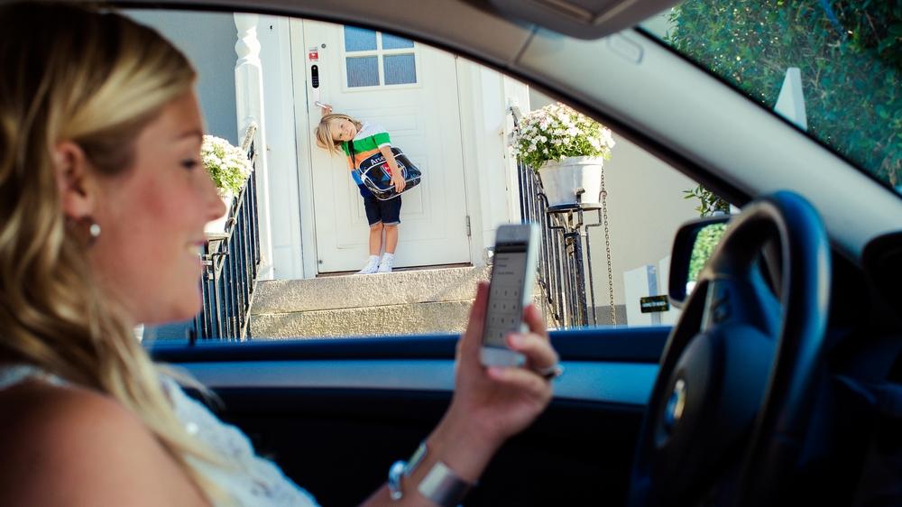 Kvinne fjernbetjener Yale Doorman med en app på mobilen for å låse inn sønnen.